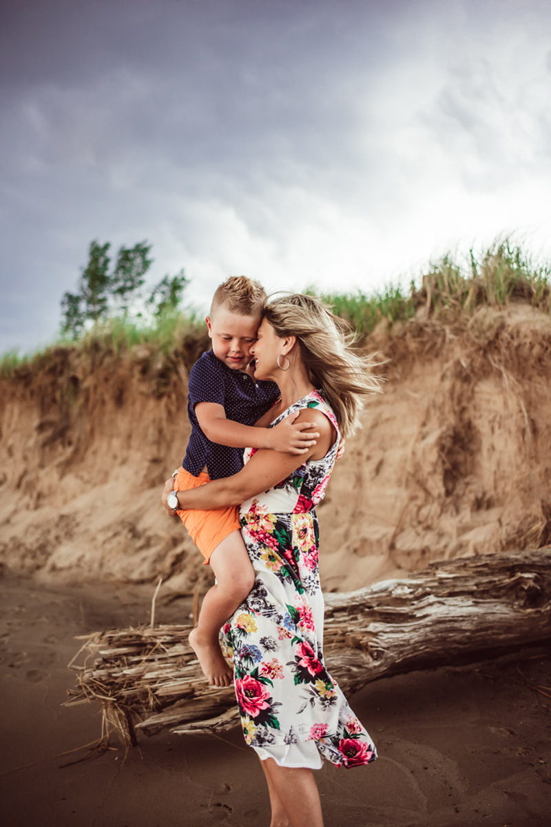 Family photography, mother in floral dress holds son outdoors near a quiet pond
