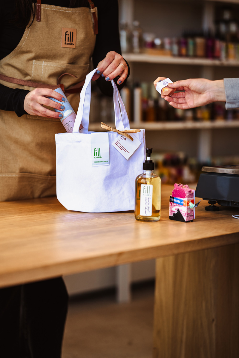 Business Photography, a store clerk assists a shopper as the clerk places items in a white cloth bag. The store has an old-time feel, bottles stocked on the shelves in the background