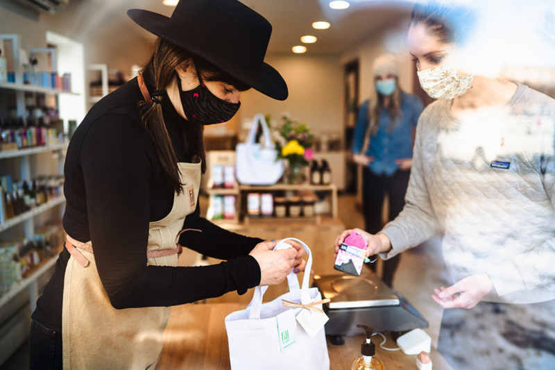 Business Photography, two women complete a transaction at a boutique store that sells beauty supplies.  both wear face masks during the covid era