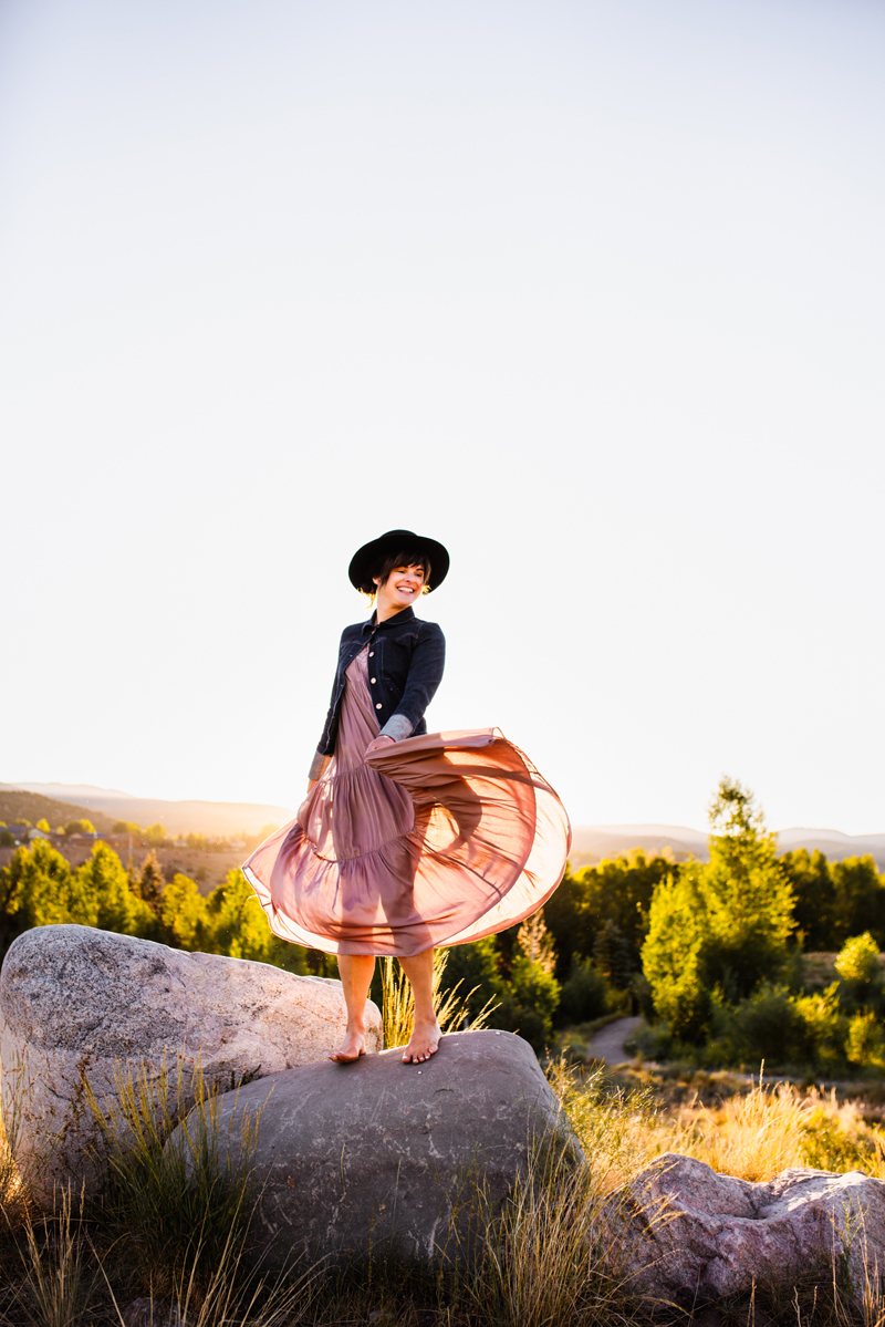 Business Photography, woman stands outside on a large rock twirling her rose skirt, she wears a blue jean jacket and a dark hat