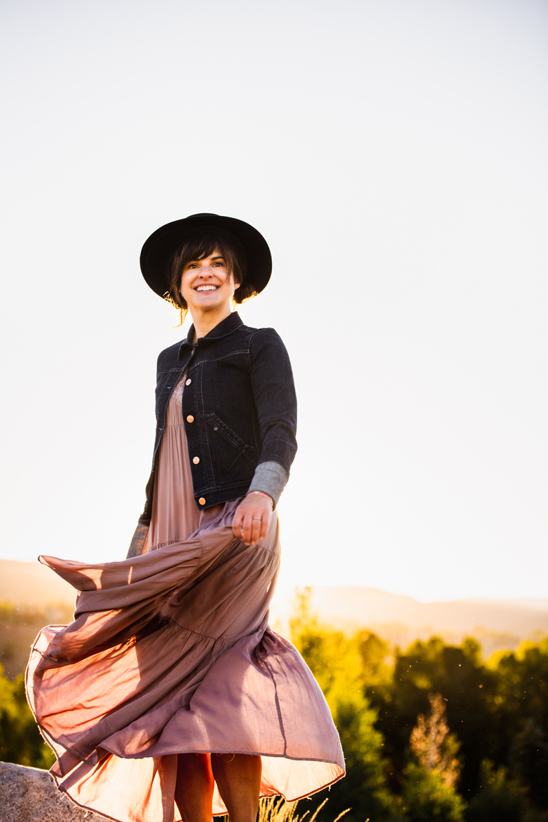 Business Photography, Young brunette woman stands smiling in the outdoors, her rose colored dress blows with the wind, she wears a blue jean jacket and dark hat