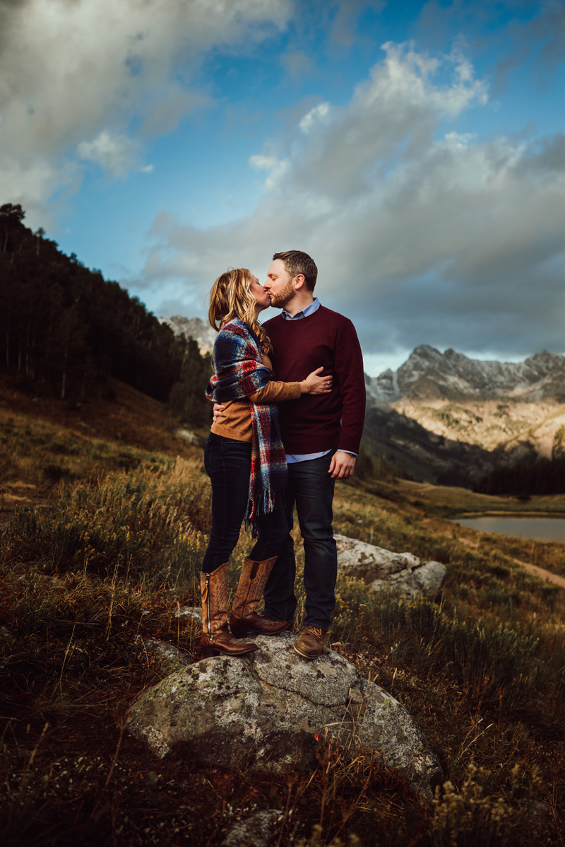 Couples Photography, Woman and man stand on rock in mountain meadow kissing
