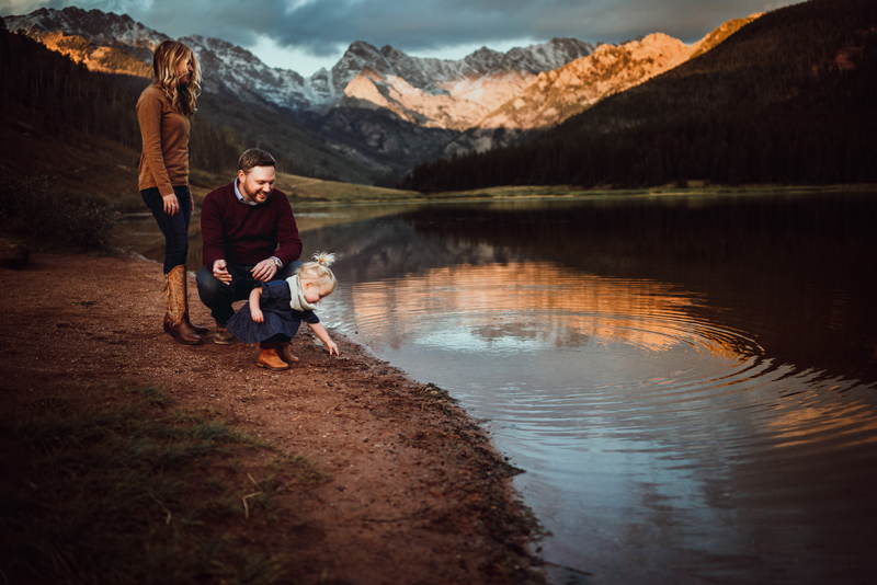 Family Photographer, two parents and their young daughter all stand next to a lake shore in the mountains