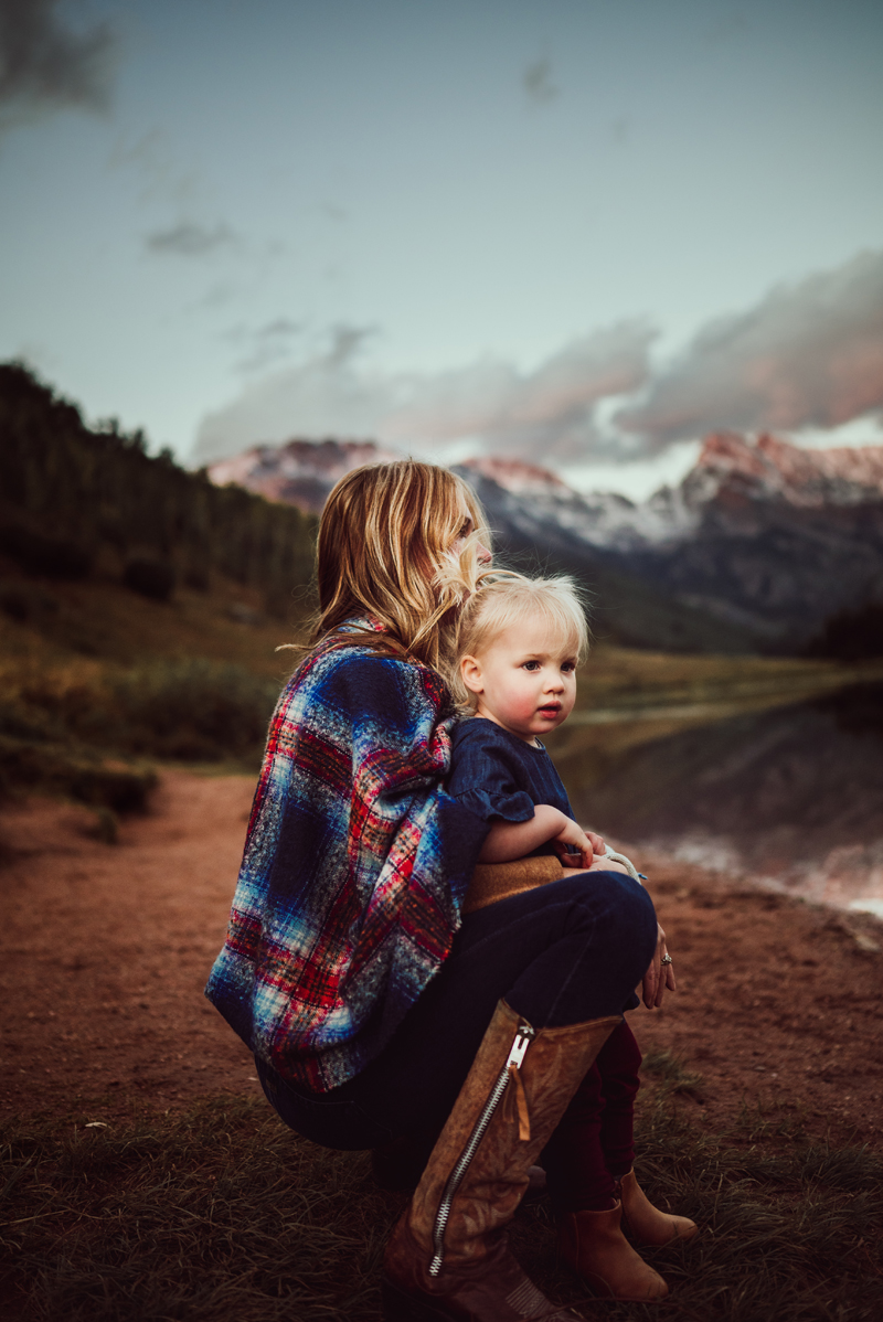 Family Photographer, Mother embraces her daughter outdoors near the mountains
