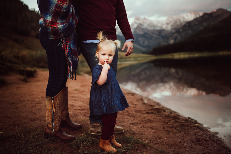 Family photography, small girl near to parents as finger in mouth pondering, they are near a mountain lake