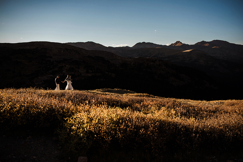 LGBTQ+ couple, in the distance, two women walk hand in hand through a golden mountain meadow