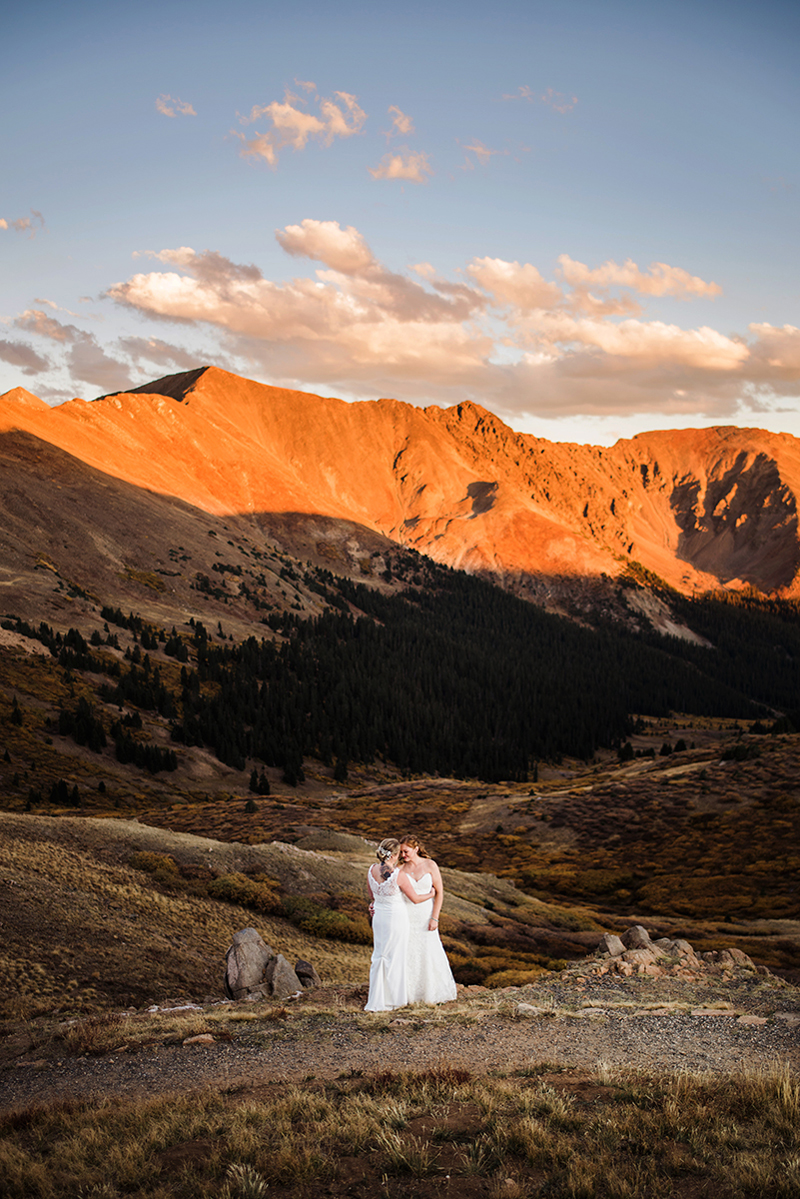 LGBTQ+ Wedding, two women in their wedding dresses stand in a mountain meadow at golden hour
