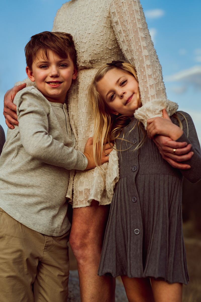 Family photography, young boy and his sister are wrapped in their mothers arms, she wears a lacy white dress