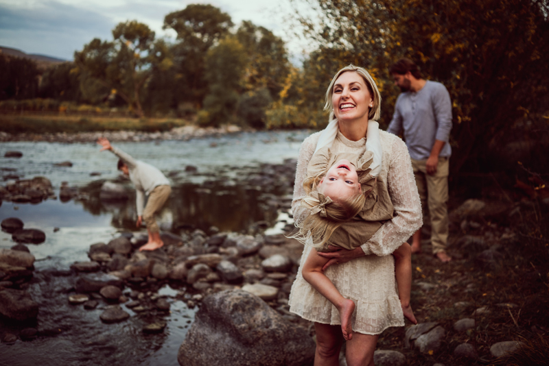 Family Photographer, Mom holds daughter, both are smiling, dad and son are adventuring near river behind them