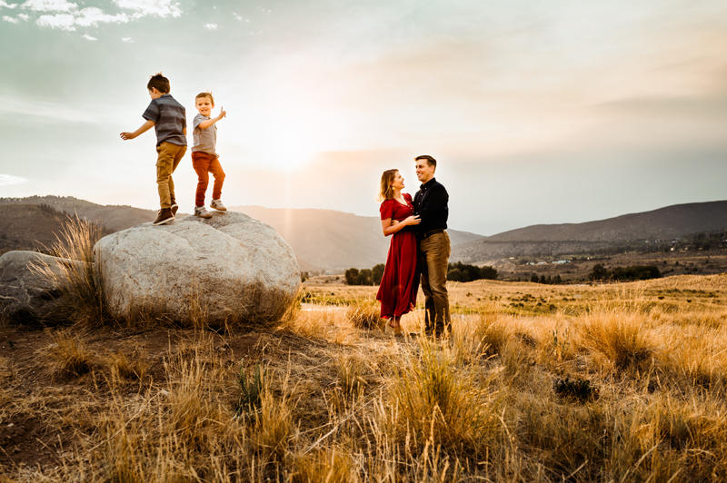 Family Photographer, two boys climb lone rocks in a field, parents embrace nearby