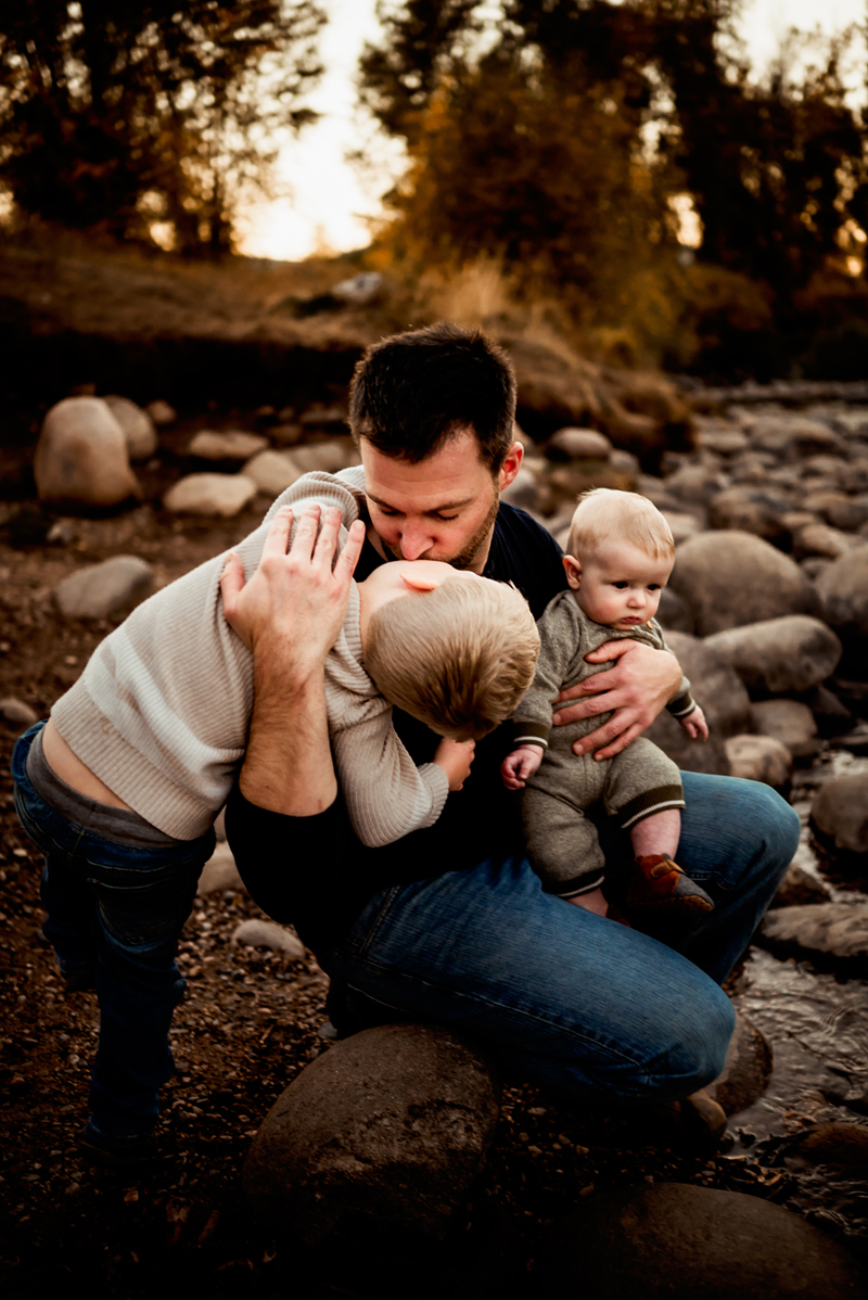 Family Photographer, father and sons sitting together on rocks