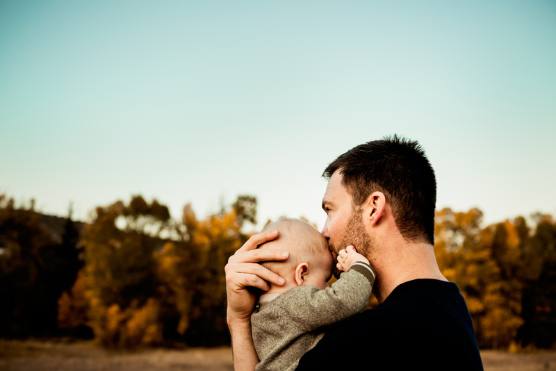 Family Photography, father kisses son on the forehead outdoors near trees