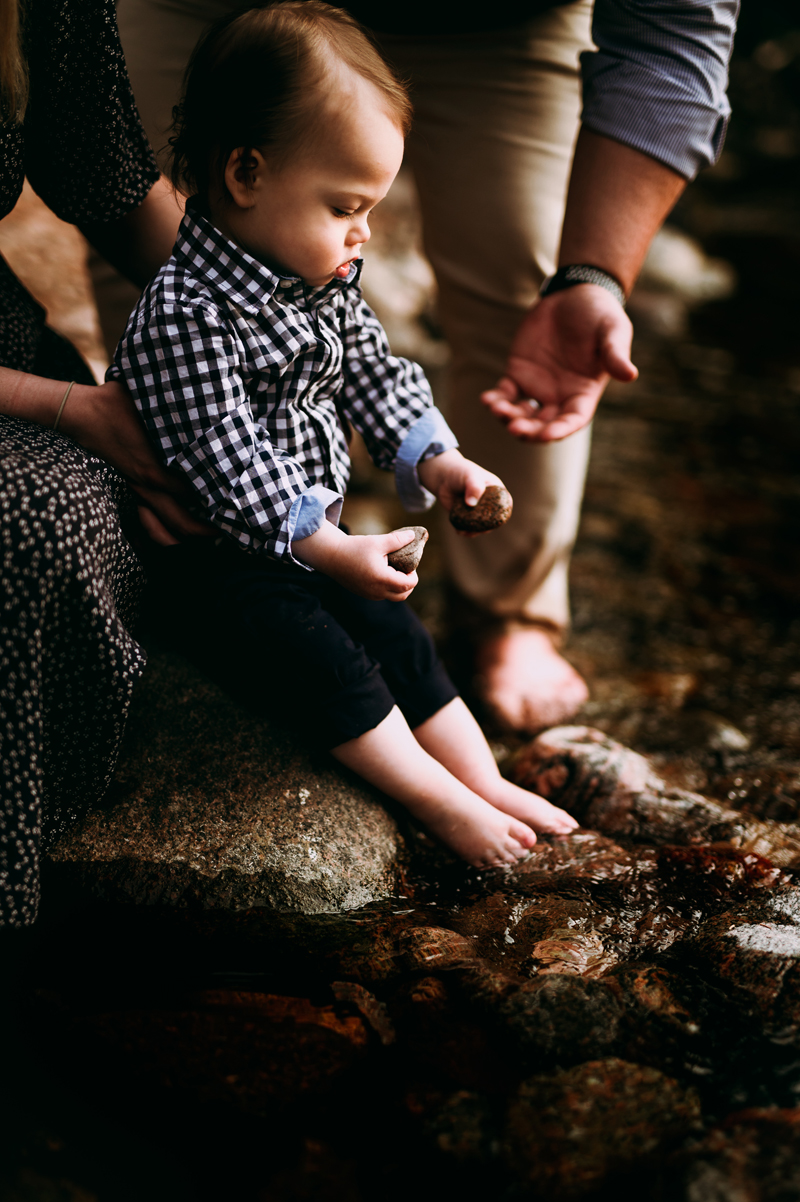 Family Photographer, a little boy held by his mother plays with two stones next to a river, his dad reaches out for it