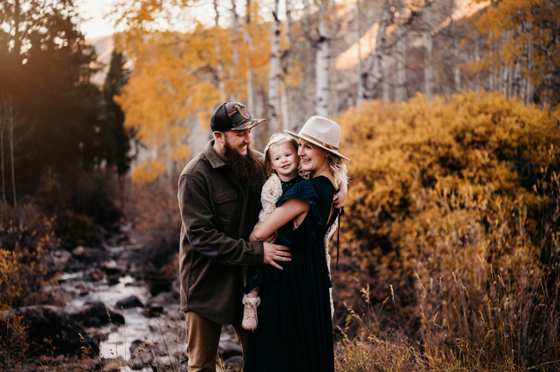 Family Photographer, mom and dad holding daughter near river in the fall