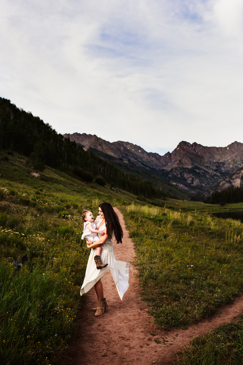 Family Photographer, Woman dances holding her baby daughter happily on a mountainside trail, both wearing white dresses and boots