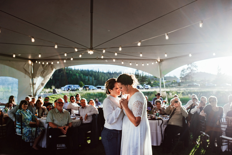 LGBTQ+ wedding, two brides dance amidst a crowd under a tent with string lights