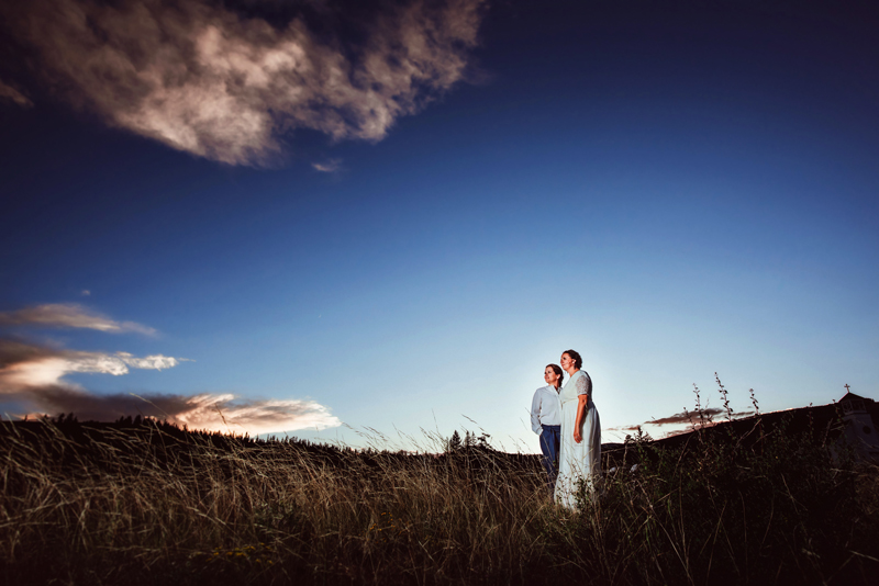 LGBTQ+ Couple, two women hold hands at dusk in a meadow, the vast sky and the silhouette of a church steeple behind them