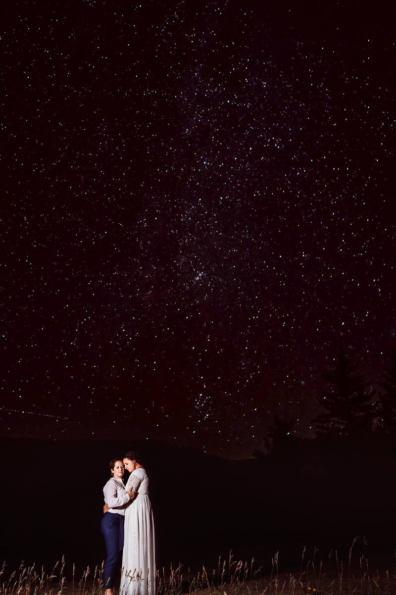 LGBTQ+ Couple, Two women hold each other close beneath a starry sky, one in a dress, the other in dress pants,