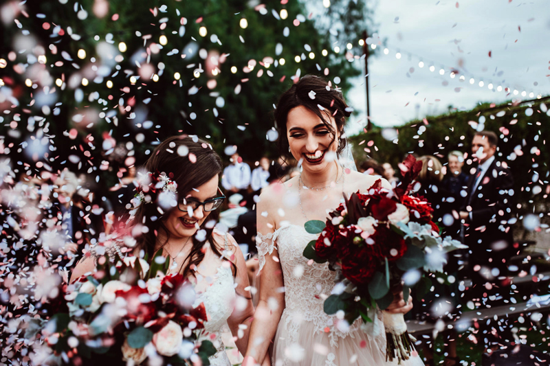 LGBTQ+ Wedding, two happy brides smiling as they walk through a cheering crowd and confetti everywhere