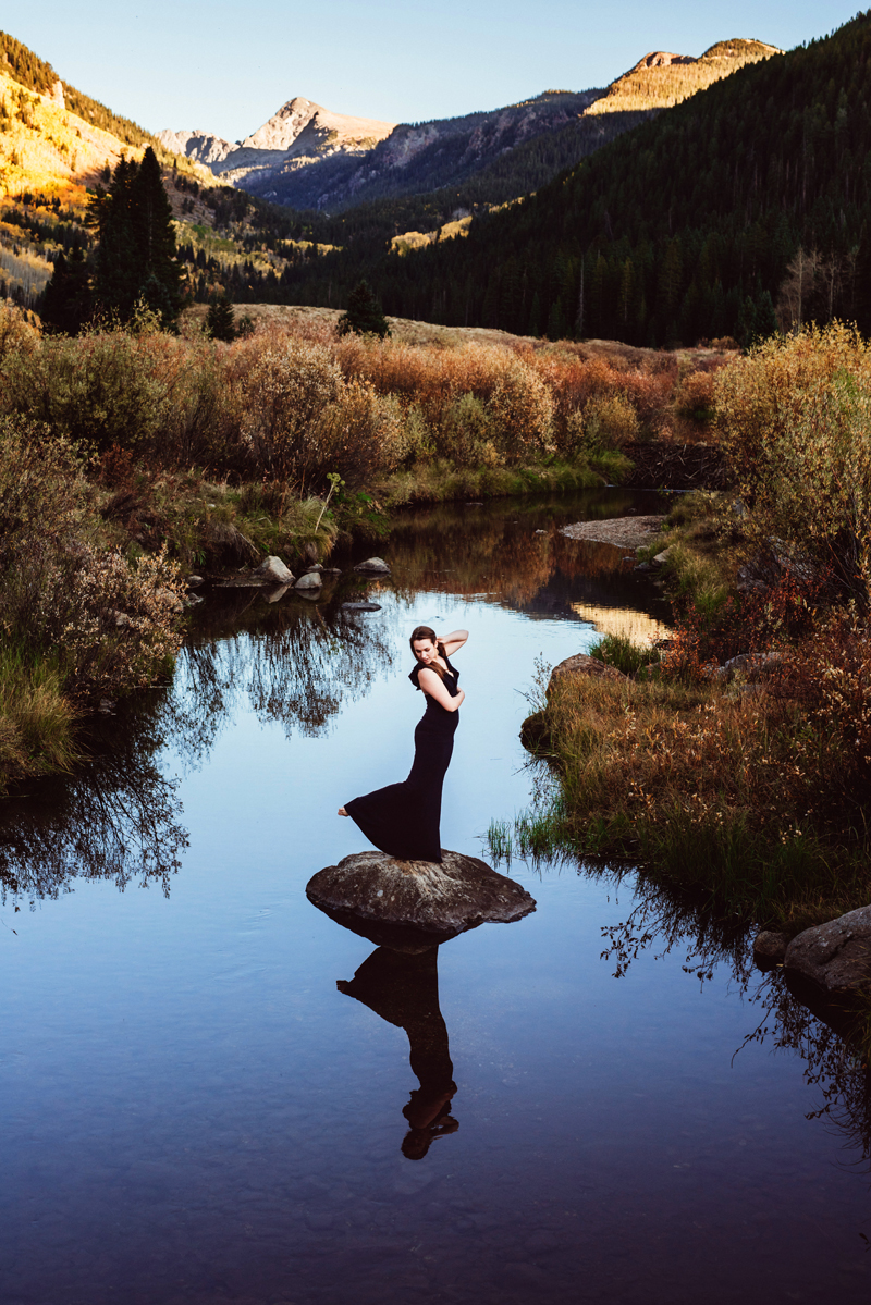 Senior Portrait, High School woman in dark dress stands on large stone in the middle of a quiet river in the mountains