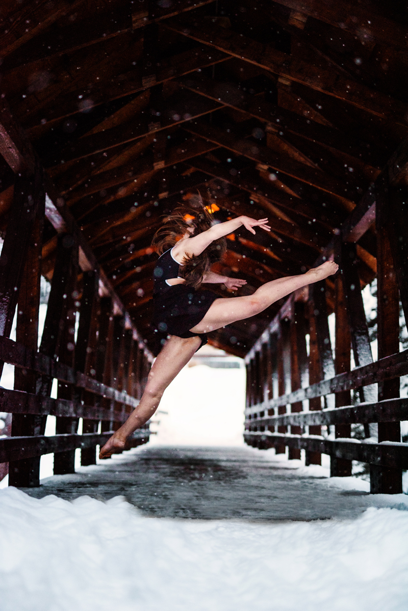 Senior Portrait, High School woman dance attire leaps into air on a snow day outside within a covered bridge