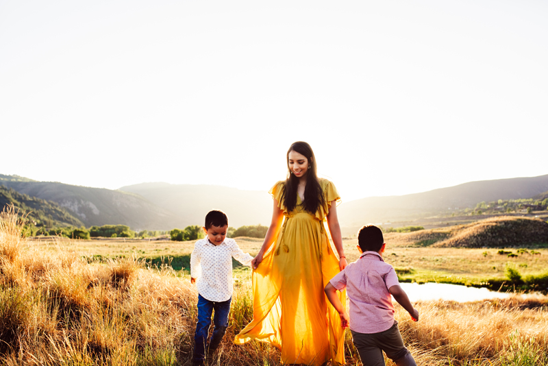 Family Photographer, woman with dark hair and a yellow dress stands in field smiling as her sons run around her