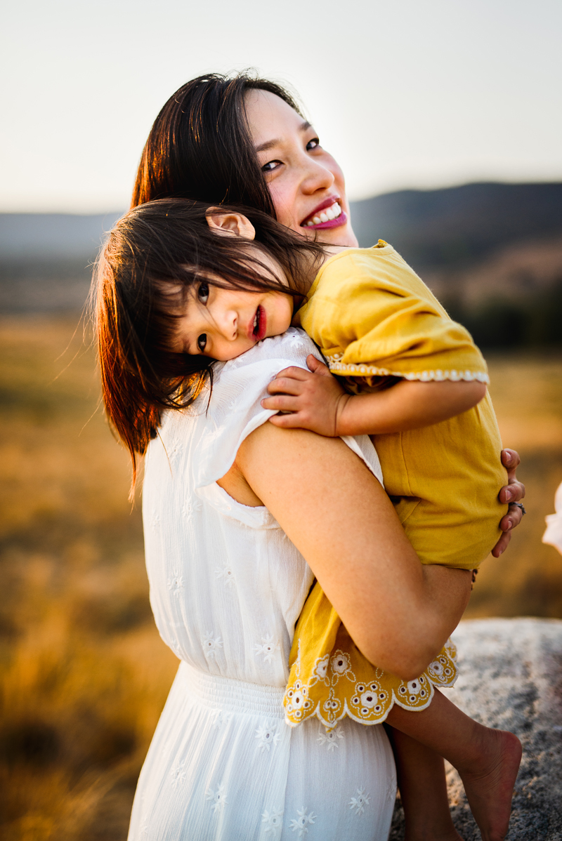 Family Photographer, Asian American woman holds her daughter, both in dresses outdoors
