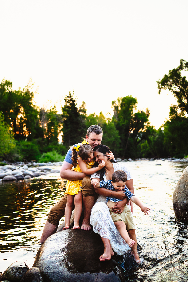 Family Photographer, a young family of four with a daughter and son all sit smiling on a large stone in a quiet river