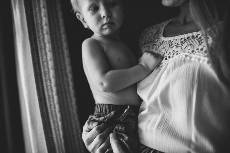 Family Photographer, young boy clutches closely to mom as she holds him