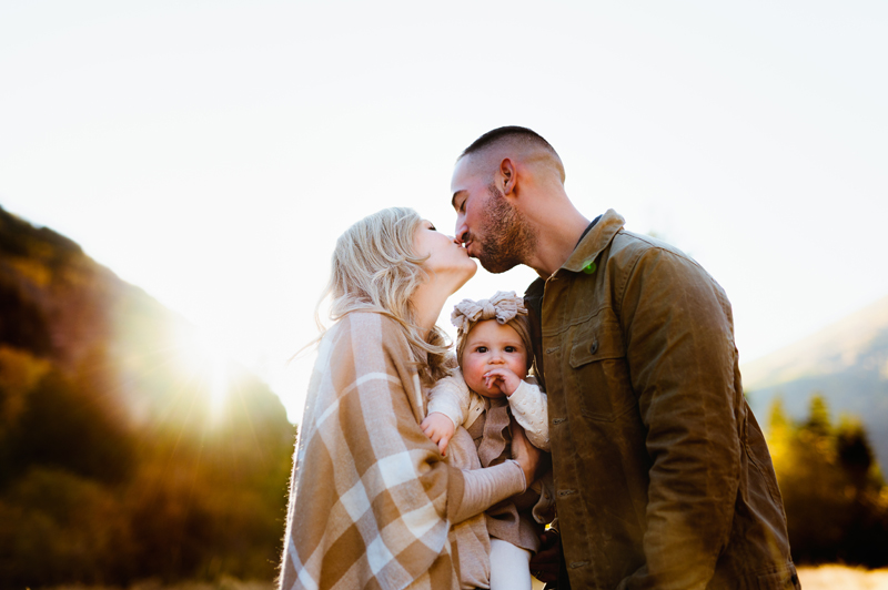 Family Photographer,  a man and a woman kiss as they hold their baby daughter close, a bow in her hair
