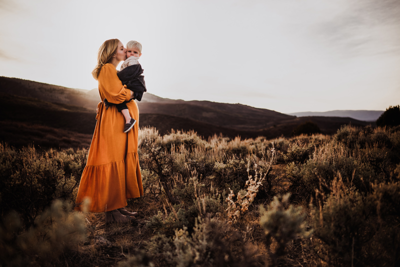 Family photography, mother holds son as she kisses him, they're standing in a meadow