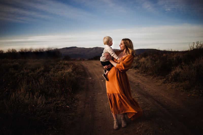 Family Photography, Young mother in orange dress holds toddler son while walking through country road