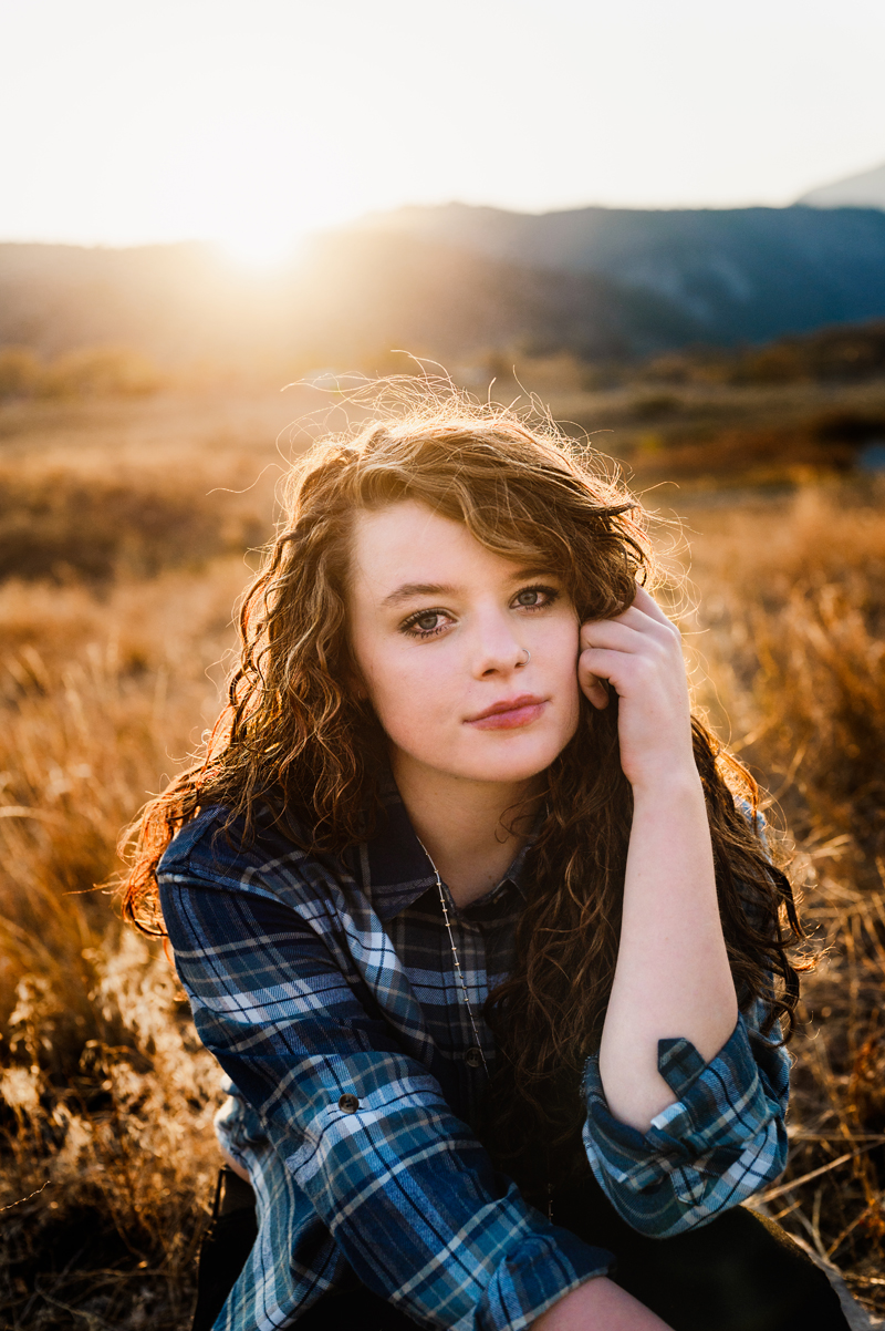 Senior Portrait, High School woman holds up wavy brunette hair outdoors as sun shines behind her