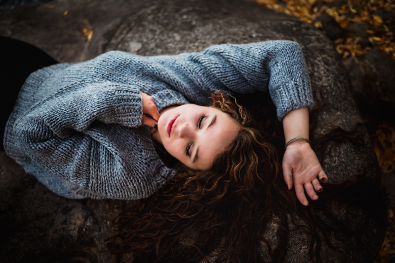 Senior Portrait, High School woman with brunette wavy hair lays content on rock