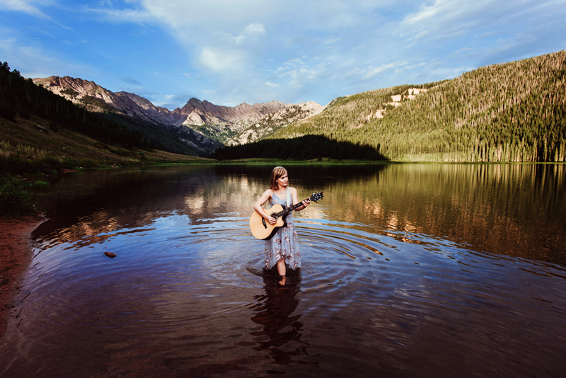 Senior Portrait, High School brunette woman stands in a lake playing guitar, mountains in the background