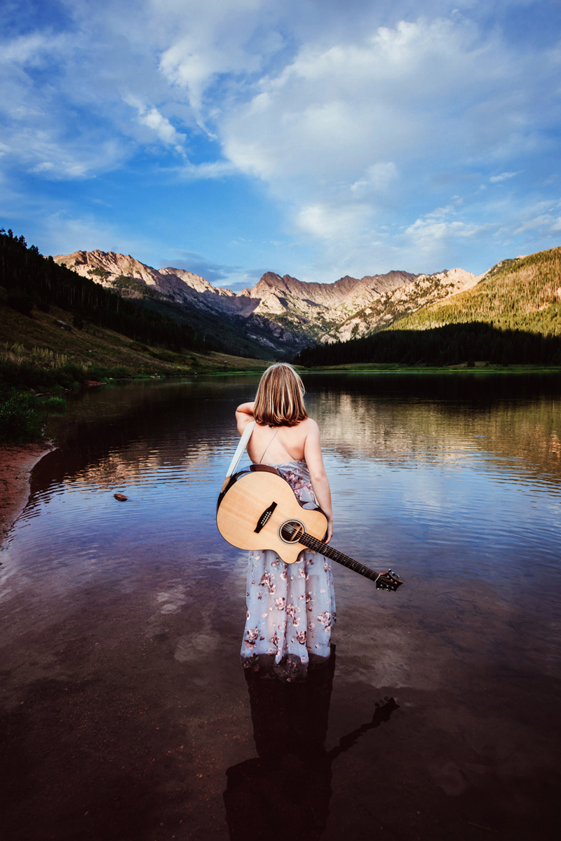 Senior Portrait, High School woman stands in a lake with guitar on back looking to mountains