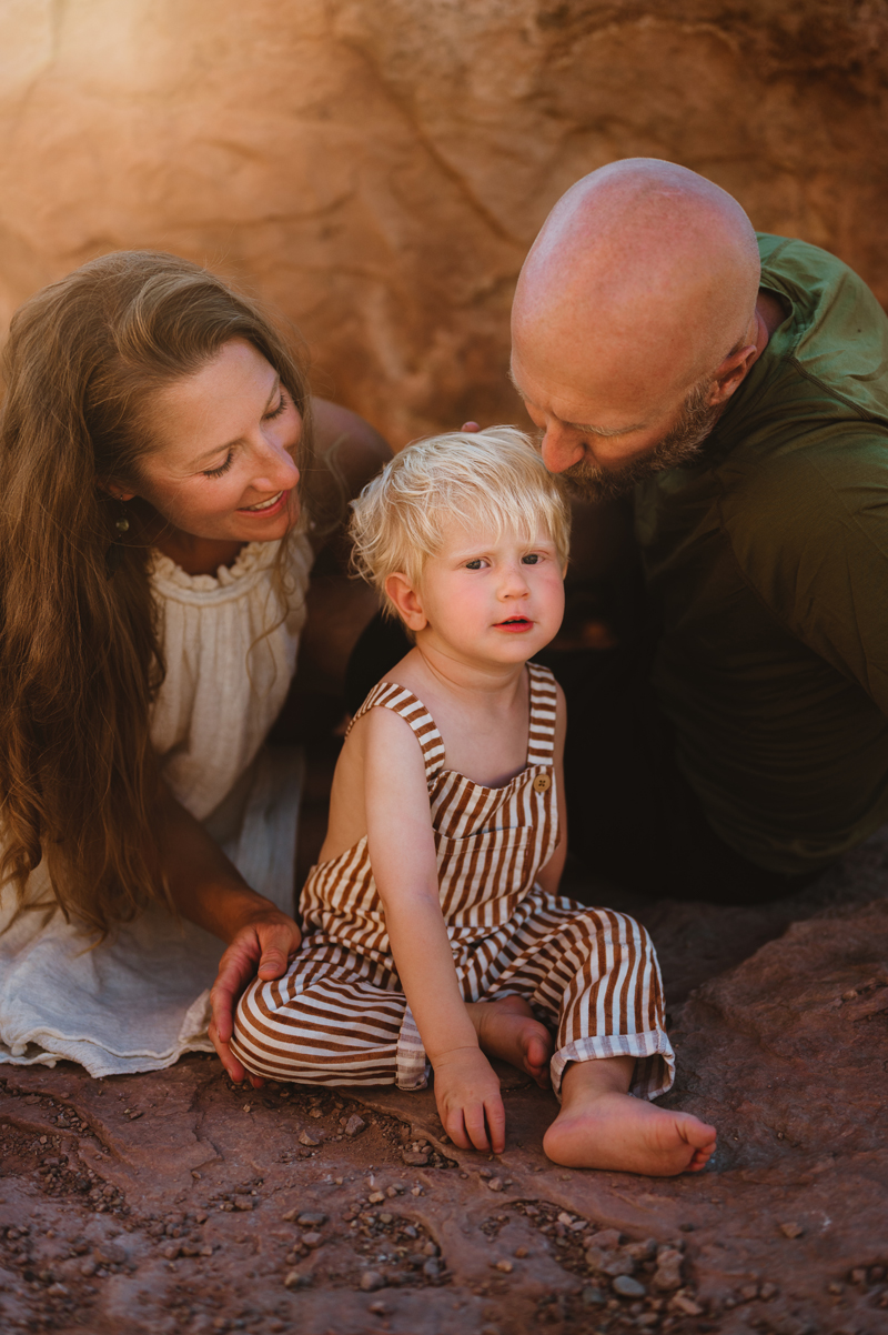 Family Photographer, mother and father sit and admire toddler son outdoors