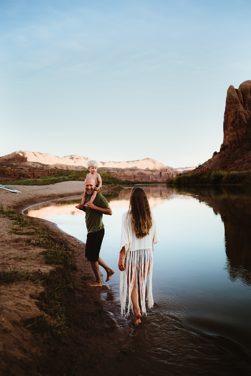 Family photography, Father with son on shoulders walks along quiet river in desert landscape, mother follows behind