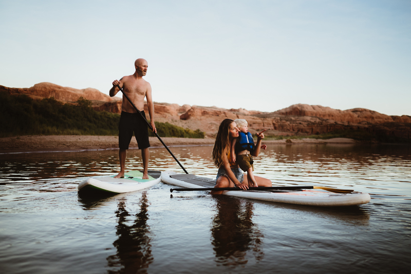 Family Photographer, Mom and son sit on a paddle board, dad stands on another next to them, they are on a lake in a desert environment