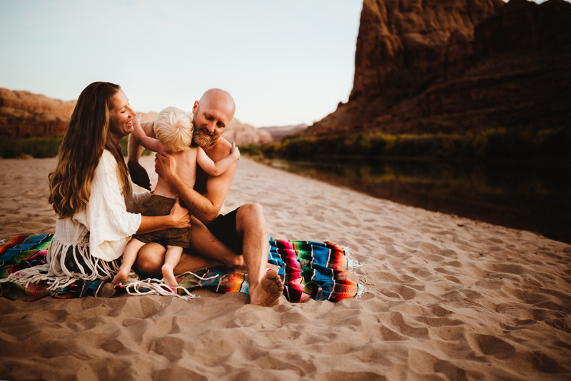 Family Photographer, Mom, dad, and child, sit on sandy river bank in Southwest USA