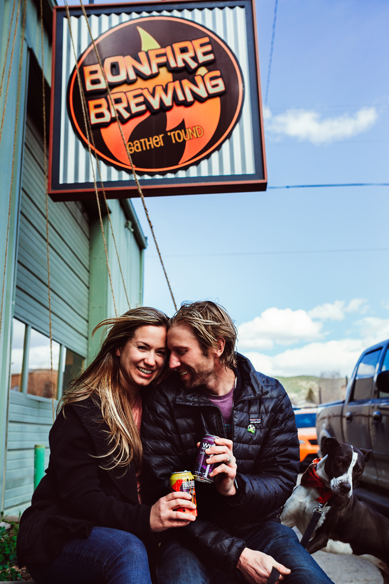 Business Photography, you man and woman snuggle with cans of coffee and their dog nearby outside Bonfire Brewing business.