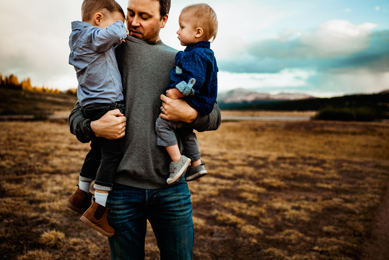Family Photographer, a dad holds two boys in a field, one of them looking down his shirt
