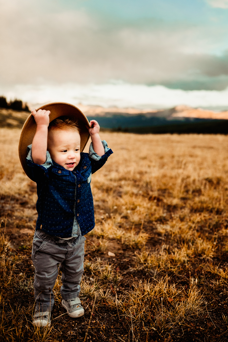 Family photography, smiling toddler holds onto his hat while out on a nature walk in the hills