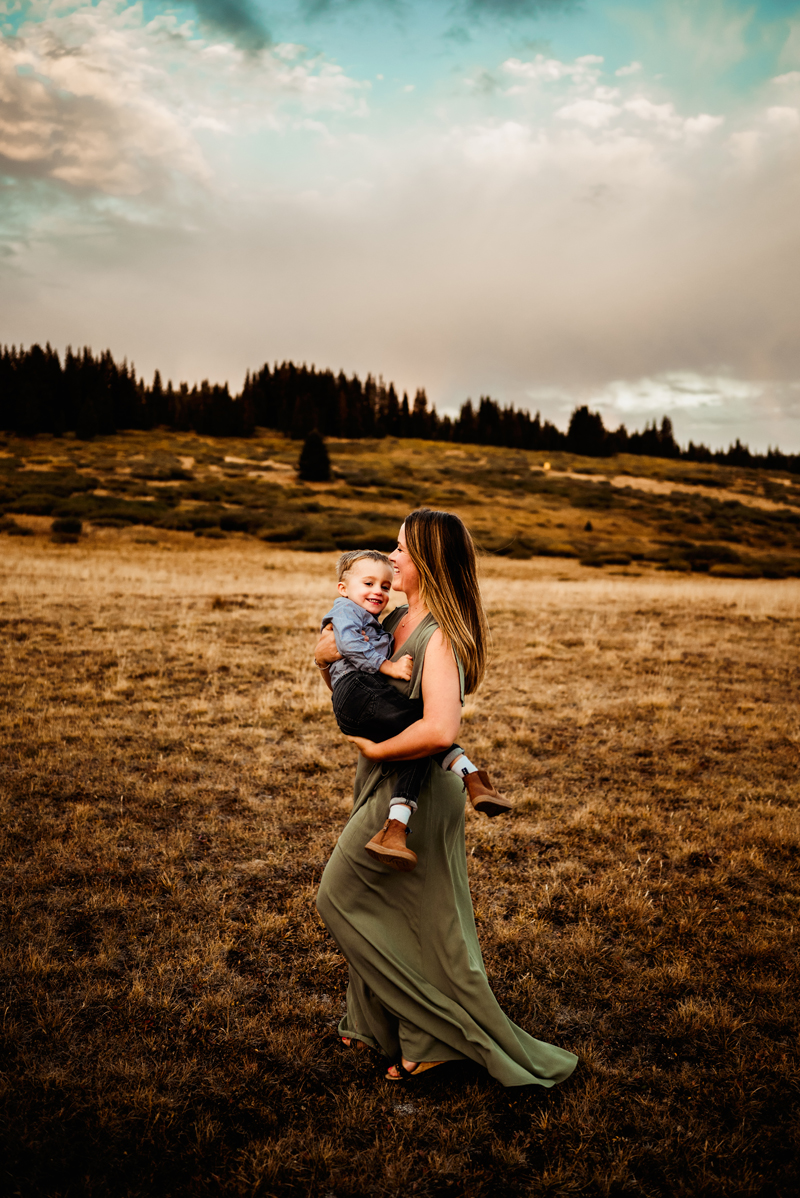 Family Photographer, Mother in olive green dress runs through field holding toddler son