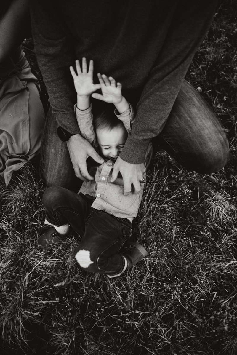 Family photography, father's hand tickle young son as he laughs as he wiggles in the grass