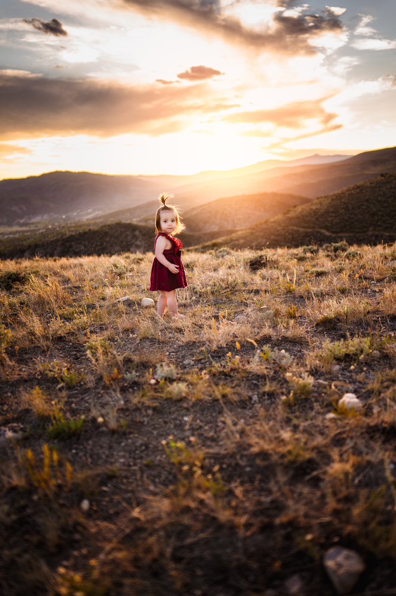 Family Photographer, a little toddler girl in a red dress looks back as she wanders on a hillside at sunset