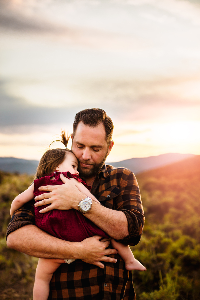 Family Photographer, Young Father holds baby daughter outdoors at sunset
