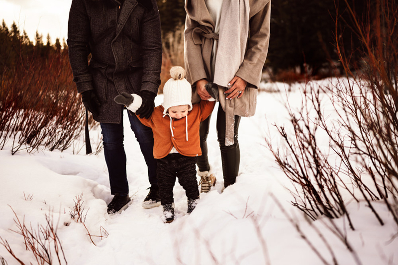 Family photography, bundled up toddler walks through the snow holding parents hands