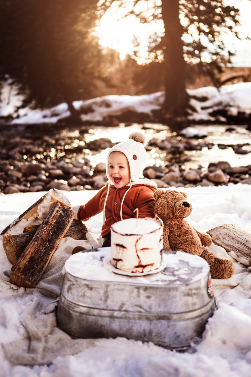 Family photography, a happy toddler sits in snow before cake, playing with teddy bear