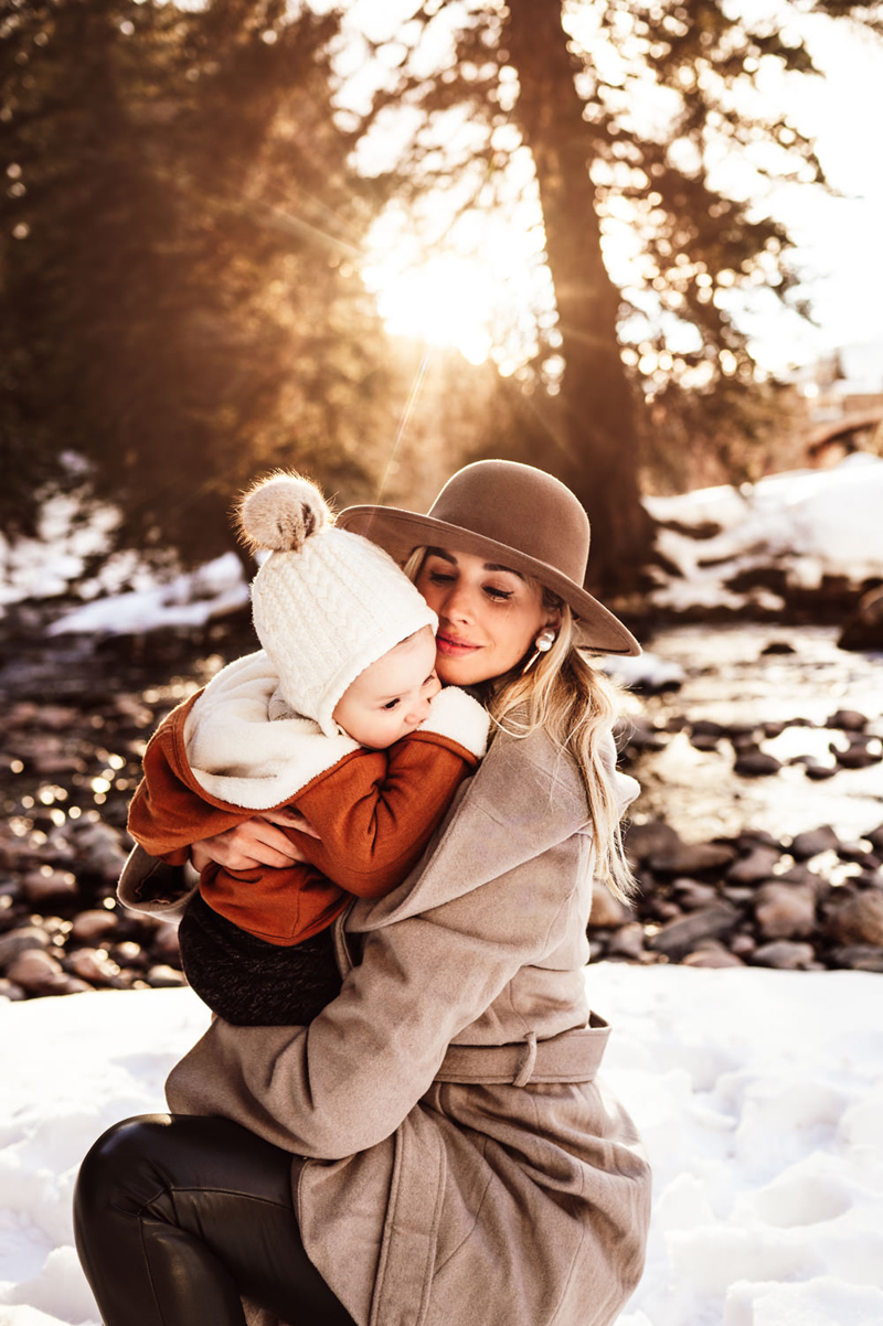 Family Photographer, Mom and baby dressed in coats kneel in a snowy forest
